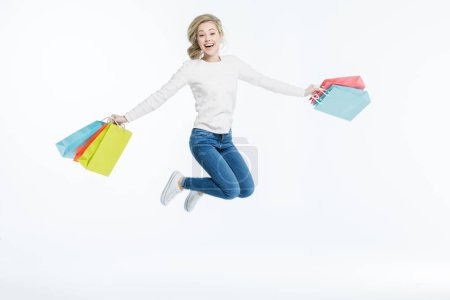 Photo for Happy young woman jumping with shopping bags isolated on white - Royalty Free Image