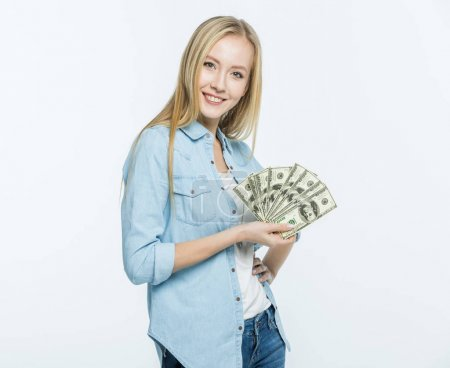 Photo for Attractive young woman holding dollar banknotes and smiling at camera  isolated on white - Royalty Free Image