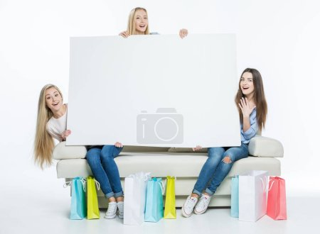 Photo for Surprised women with shopping bags holding blank white card  isolated on white - Royalty Free Image