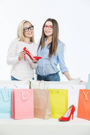 Photo for Smiling young women with shopping bags holding fashionable red shoe  isolated on white - Royalty Free Image