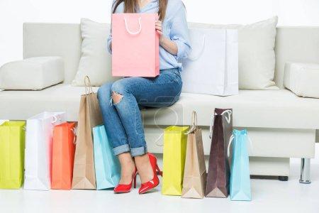 Photo pour Vue partielle de la jeune femme assise sur le canapé avec sac à provisions rose isolé sur blanc - image libre de droit