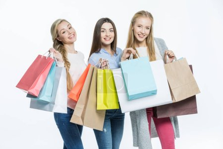Photo pour Attractive young women with colorful shopping bags smiling at camera isolated on white - image libre de droit