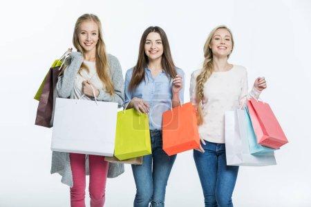 Photo pour Trois jeunes femmes avec des sacs colorés souriant à la caméra isolée sur blanc - image libre de droit