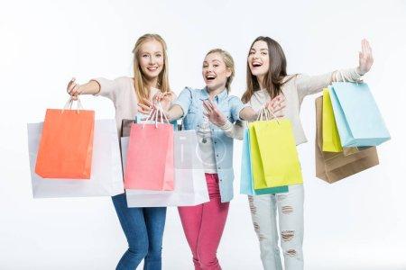 Photo pour Jeunes femmes excitées avec des sacs colorés souriant à la caméra isolée sur blanc - image libre de droit