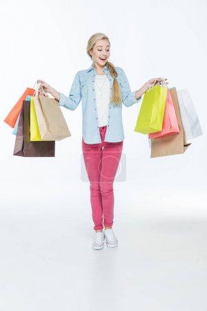 Photo pour Portrait pleine longueur de jeune femme excitée avec des sacs à provisions isolés sur blanc - image libre de droit