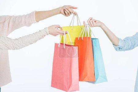 Photo pour Vue partielle des mains féminines tenant des sacs à provisions colorés isolés sur blanc - image libre de droit