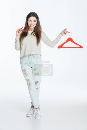 Photo for Beautiful young woman holding red hanger and eyeglasses  isolated on white - Royalty Free Image