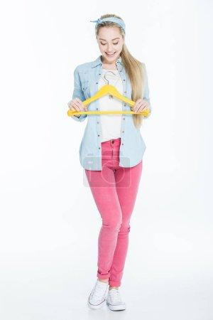 Photo pour Joyeux jeune femme tenant cintre jaune isolé sur blanc - image libre de droit