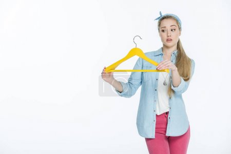 Photo for Confused young woman holding yellow hanger  isolated on white - Royalty Free Image