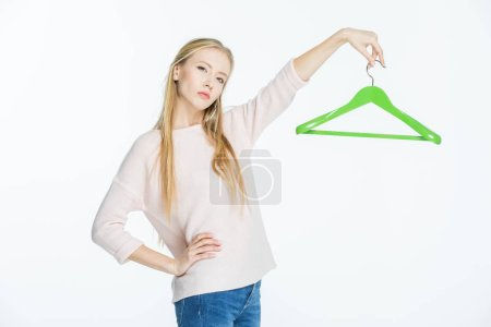 Photo for Pensive young woman holding green hanger isolated on white - Royalty Free Image