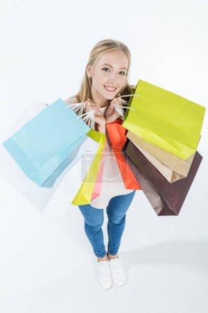 Photo pour Heureuse jeune femme tenant des sacs à provisions et regardant la caméra isolée sur blanc - image libre de droit