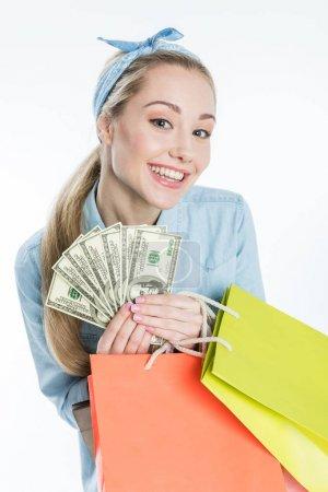 Photo pour Joyeux jeune femme tenant des sacs à provisions et des billets en dollars isolés sur blanc - image libre de droit