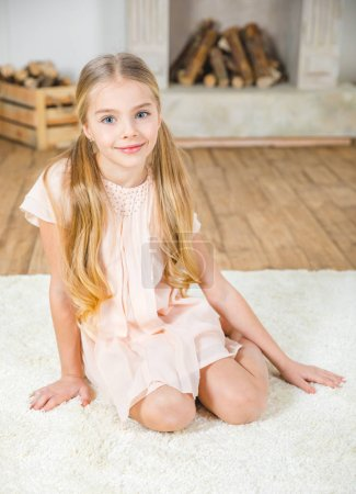 Photo for Cute little girl sitting on white carpet and smiling at camera - Royalty Free Image