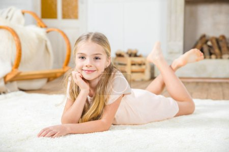 Photo for Cute little girl lying on white carpet and smiling at camera - Royalty Free Image