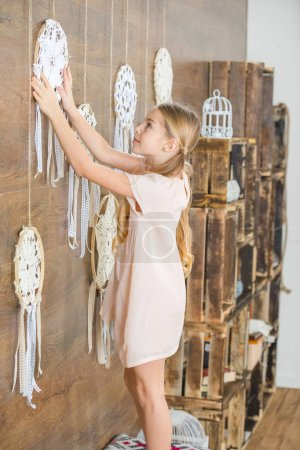 Photo for Side view of cute little girl decorating room with white decorative dreamcatchers - Royalty Free Image