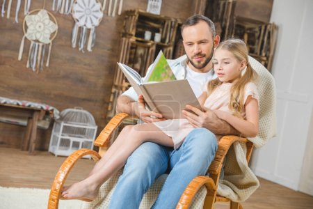 Photo for Father and daughter sitting together in rocking chair and reading book - Royalty Free Image