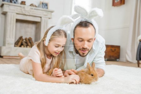 Father and daughter playing with rabbit