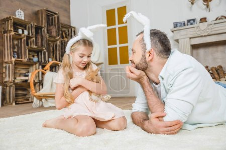Photo for Happy father and daughter in bunny ears playing with rabbit at home - Royalty Free Image