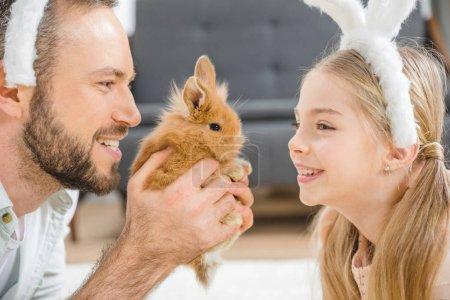 Photo pour Gros plan portrait de père et fille dans des oreilles de lapin jouant avec le lapin - image libre de droit