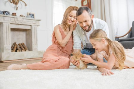 Photo for Happy family playing with cute fluffy rabbit on white carpet at home - Royalty Free Image