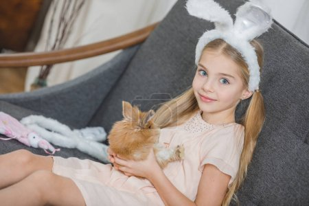 Photo for Little girl holding cute fluffy rabbit and smiling at camera - Royalty Free Image