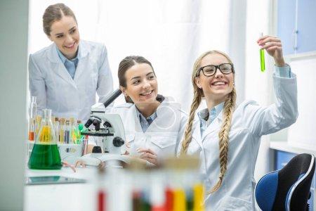 Photo pour Jeunes femmes scientifiques souriantes regardant des éprouvettes avec réactif en laboratoire chimique - image libre de droit