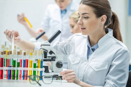 Photo for Young female scientist working with microscope in chemical laboratory - Royalty Free Image