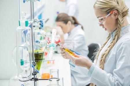 Photo pour Jeune femme scientifique dans la couche protectrice de verres et de laboratoire en regardant des tubes à essai en laboratoire - image libre de droit
