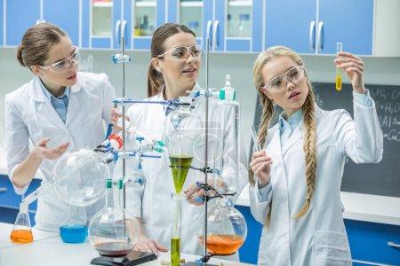 Photo pour Jeunes femmes scientifiques dans des lunettes de protection regardant le tube à essai avec réactif en laboratoire - image libre de droit
