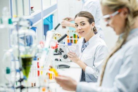 Photo pour Jeune femme scientifique travaillant au microscope et regardant la caméra en laboratoire - image libre de droit