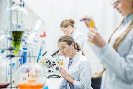 Photo pour Jeune femelle scientifique travaillant au microscope en position assise entre collègues en laboratoire - image libre de droit