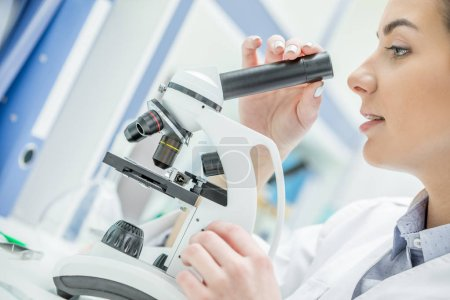 Photo pour Profil de jeune femme scientifique travaillant avec microscope de laboratoire - image libre de droit