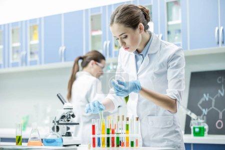 Photo pour Femmes scientifiques travaillant avec des réactifs en tubes à essai en laboratoire de chimie - image libre de droit