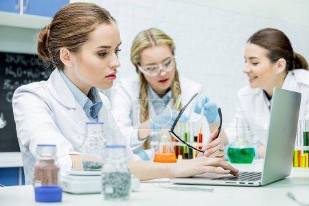 Photo pour Concentré de femme scientifique travaillant sur ordinateur portable dans le laboratoire de chimie - image libre de droit