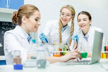 Photo for Female scientists working with laptop and reagents in chemical laboratory - Royalty Free Image