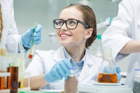 Photo pour Attrayant femme scientifique en lunettes travaille avec ses collègues de laboratoire - image libre de droit