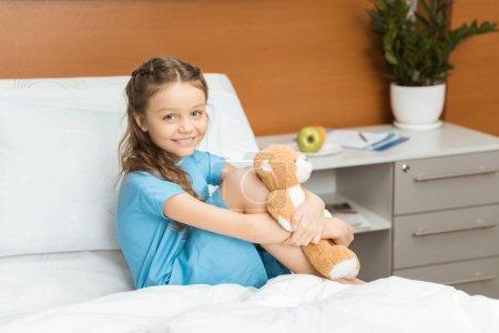 Photo pour Petite patiente avec ours en peluche assise sur le lit à l'hôpital - image libre de droit