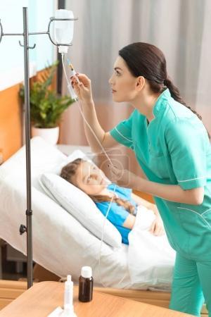 Photo pour Médecin avec comptoir de chute et petit patient allongé sur le lit à l'hôpital - image libre de droit