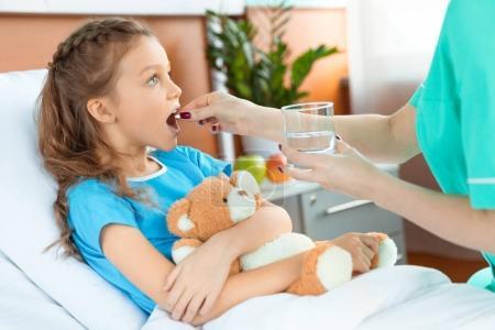 Photo pour Médecin donnant la pilule à un petit patient avec un ours en peluche couché sur le lit à l'hôpital - image libre de droit