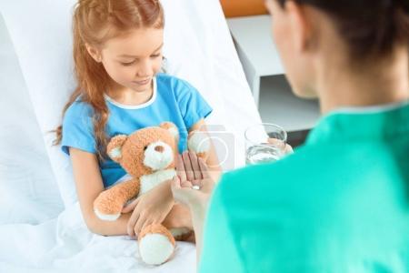 médico dando píldora al paciente