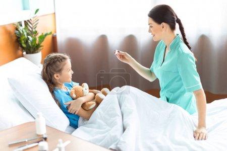 Photo pour Femme infirmière vérifier la température de la petite fille malade dans le lit d'hôpital - image libre de droit