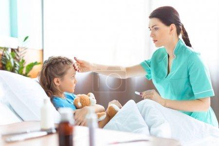 Photo pour Vue latérale de l'infirmière vérifiant la température de la petite fille malade dans le lit d'hôpital - image libre de droit