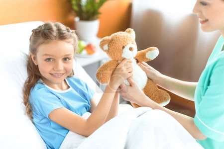 Photo for Cropped shot of nurse giving teddy bear to smiling little girl in hospital - Royalty Free Image