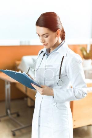 Young woman doctor with clipboard
