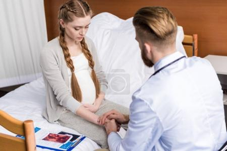 Doctor and upset pregnant woman