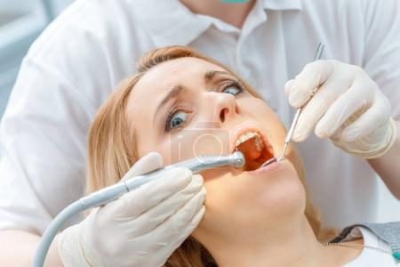 Dentist curing scared patient