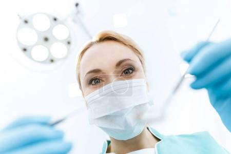Photo for Professional dentist in medical mask working in clinic and looking at camera - Royalty Free Image