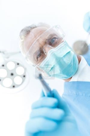 Photo for Professional mature dentist in medical mask and protective glasses looking at camera - Royalty Free Image