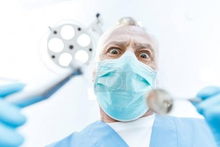 Photo for Excited professional dentist in medical mask holding dental tools and looking at camera - Royalty Free Image
