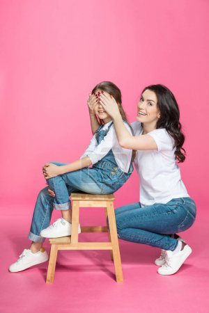 Photo for Happy mother covering eyes to cute smiling daughter sitting on stool isolated on pink - Royalty Free Image